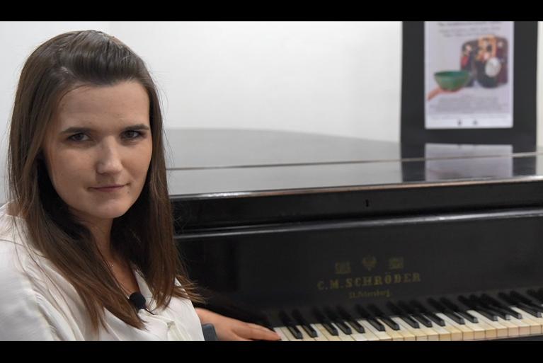 Pracowniczka GOKu na tle fortepianu